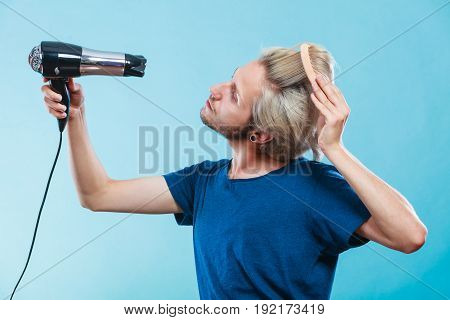 Style and fashion. Young trendy male hairstylist barber with new idea of look changing. Blonde man holding hair dryer and comb creating new hairdo on blue