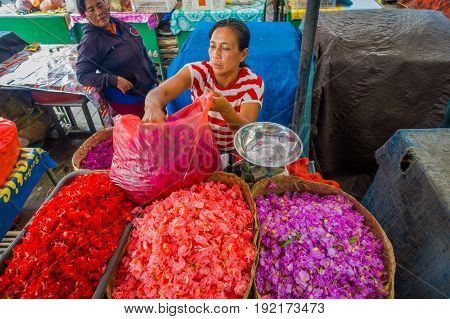BALI, INDONESIA - MARCH 08, 2017: Unidentified people in outdoors Bali flower market. Flowers are used daily by Balinese Hindus as symbolic offerings at temples, inside of colorful baskets.