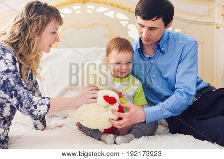 Family, parenthood and children concept - Happy mother, father and son playing together with teddy bear on bed in bedroom at home