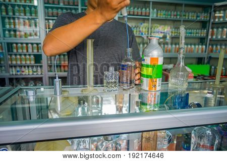 BALI, INDONESIA - MARCH 08, 2017: Man using pipettes for mixing essences to prepare perfumes for the permuse store in Denpasar Indonesia.