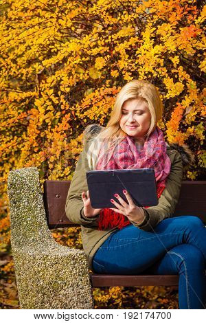 Woman relaxing sitting on bench in park during autumn weather using tablet pc checking social media.