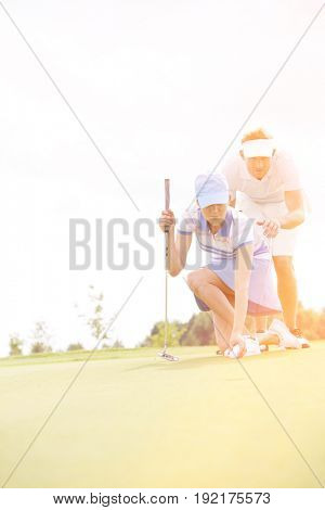 Man assisting woman placing ball on golf course against sky