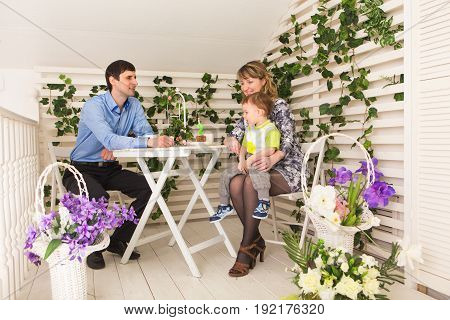family, parenthood, happy birthday and holiday concept - happy parents and child at a table drinking tea and eating cake