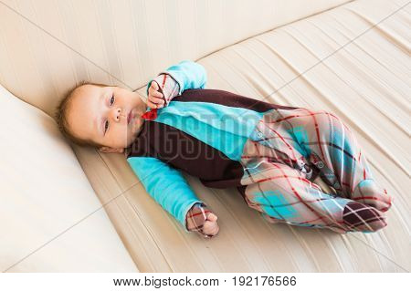 Adorable baby boy with red hair and blue eyes. Newborn child lyling in couch