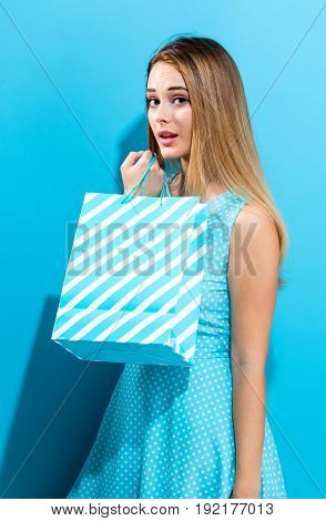 Young woman holding a shopping bag on a blue background