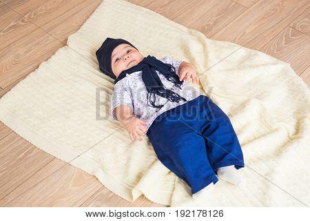 Cute baby boy lying on a floor.