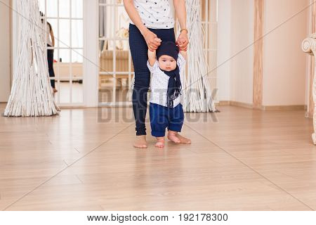 Mom teaching her son's first baby steps indoors.