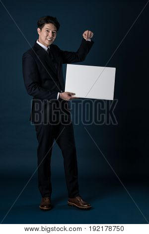 Full body shots of an Asian business man holding a whiteboard