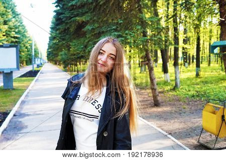 Astonishment. A young pretty girl with light brown hair depicts different emotions. The girl is dressed in a black leather jacket and a white dress under her. She does this by walking in the spring park. Sunny spring evening.