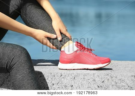 Young sporty woman suffering from pain in leg outdoors, closeup