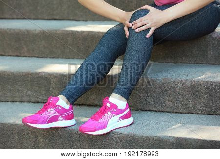 Young woman suffering from pain in leg while sitting on steps outdoors
