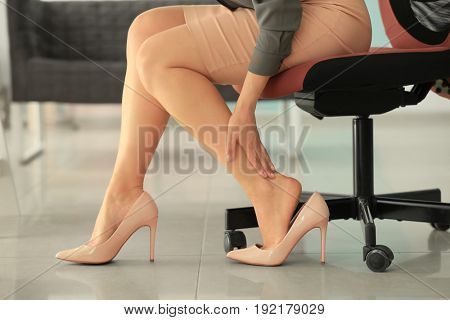 Young woman suffering from leg pain in office because of uncomfortable shoes