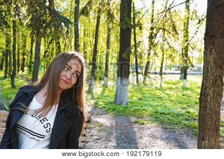 Fear. A young pretty girl with light brown hair depicts different emotions. The girl is dressed in a black leather jacket and a white dress under her. She does this by walking in the spring park. Sunny spring evening.