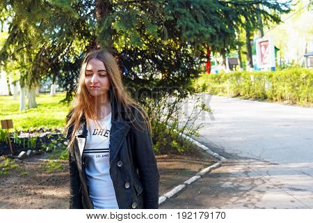 Relaxation. A young pretty girl with light brown hair depicts different emotions. The girl is dressed in a black leather jacket and a white dress under her. She does this by walking in the spring park. Sunny spring evening.