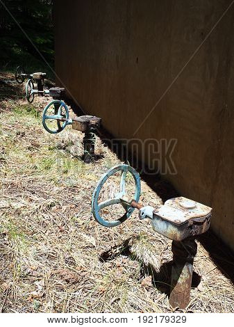 A row of old pipe valves at the Wizard Falls Fish Hatchery on the Metolius River on a sunny summer day.