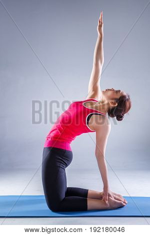 Portrait of gorgeous young woman practicing yoga in studio with on dark background woman seeking enlightenment through meditationrelaxed girl performing yoga routine.