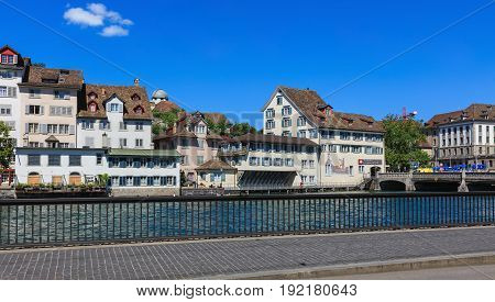 Zurich, Switzerland - 18 June, 2017: historic buildings along the Limmat river, people on the embankment of the river. Zurich is the largest city in Switzerland and the capital of the Swiss canton of Zurich.