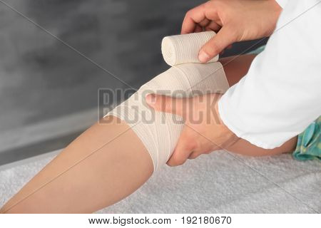 Doctor applying bandage onto patient's leg in clinic, closeup