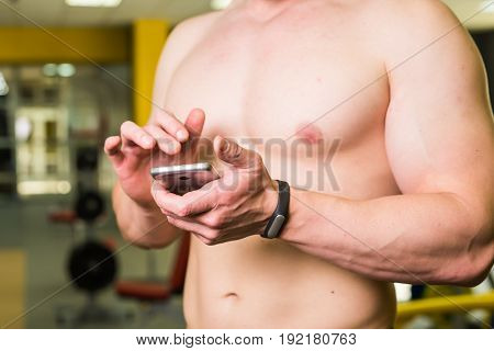 Close-up of Sportive Man After Workout Session Checks Fitness Results Smartphone. Sport Tracker Wristband Arm.Training hard inside gym