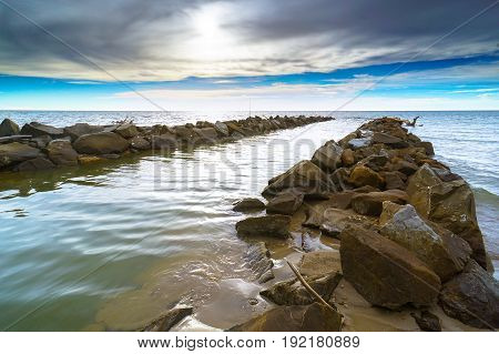 Landscape with sea blue sky sun,colorful sky clouds with the stone embankment during beautiful sunset in Labuan island,Malaysia.