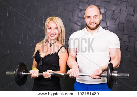 sport, bodybuilding, lifestyle and people concept - smiling man and woman with barbell.