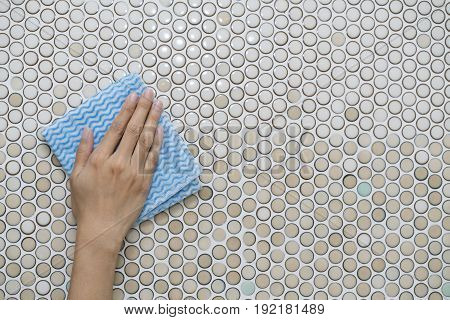 Cleaning tile wall by woman hand, close up