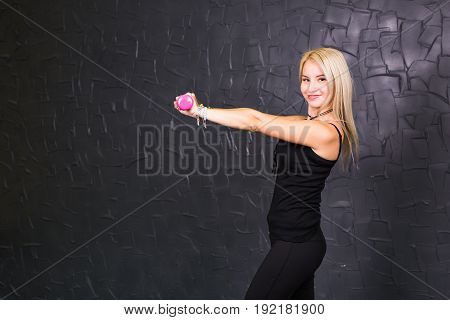 Sport woman trains her shoulders using pink dumbbells. Athletic girl holding a dumbbell pink on a black background.