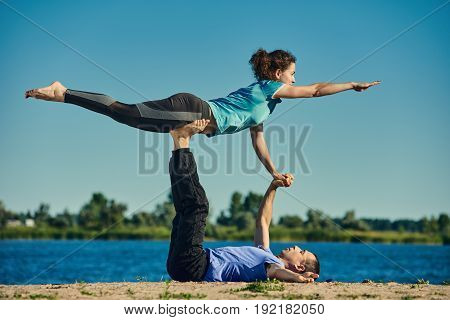 Healthy young man and woman doing different yoga poses together
