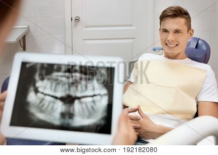 Young male patient in dentist chair waiting for doctor diagnosis
