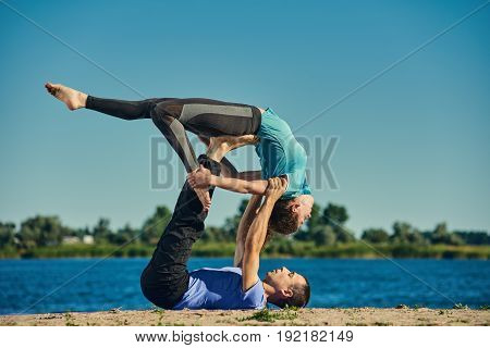 Young beautiful man and woman practicing Dandasana and Dhanurasana