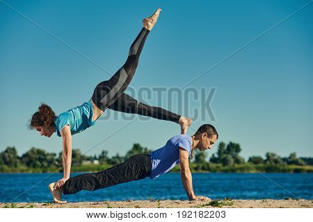 Two young people doing yoga asana Chaturanga Dandasana