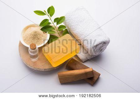Ayurvedic handmade  Sandalwood both soap or chandan sabun with sandalwood sticks, ubtan or scrub or powder, oil and white towel, selective focus