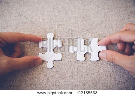 Hands holding puzzle pieces business concept background