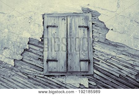 old wooden window on weathered wall that show structural timber-frame and masorny of traditional ottoman construction in Montenegro