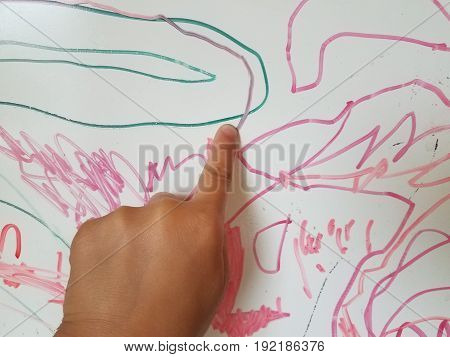 child's finger pointing to red and green lines on whiteboard