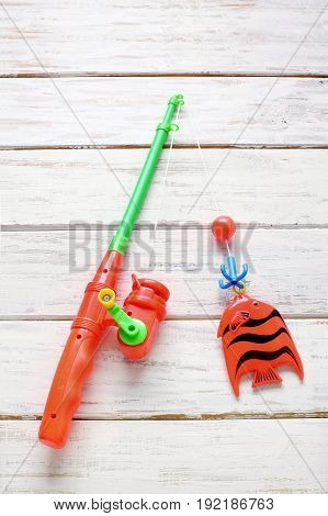 Plastic Fishing Toy on a Wooden Background