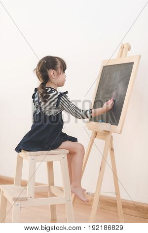 Happy Asian Girl Kid Draw Cartoon With Chalk On Blackboard For Learning At Home. Photo For Kid Educa