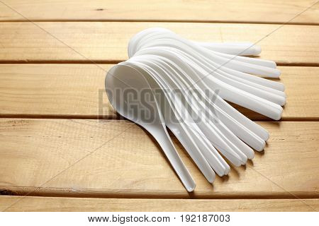 White Plastic Soup Spoons on Wooden Background