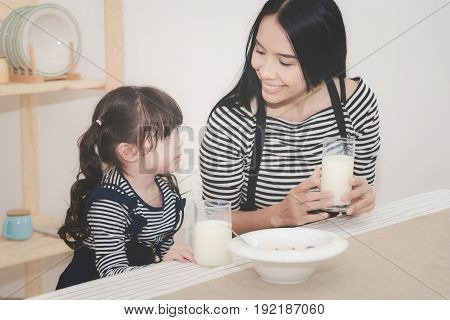Happy Family Of Asian Mom Is Drinking Milk With Her Cute Daughter In The Morning. Photo Series Of Fa