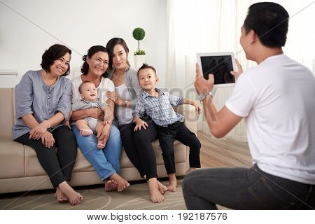 Portrait of big Asian family with two kids posing for photo at home, all smiling happily looking at father holding digital tablet  Family Portrait