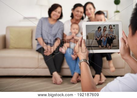 Portrait of big Asian family taking photo at home, all smiling happily on  tablet screen