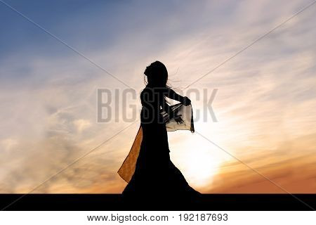 A silhouette of a beautiful young woman dancer outside at sunset praising God.