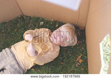 A happy young boy child is playing outside on a summer day laying in the grass in a cardboard box fort.