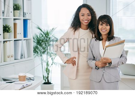 Portrait of two attractive middle-aged businesswomen looking at camera with wide smiles while standing in modern open plan office