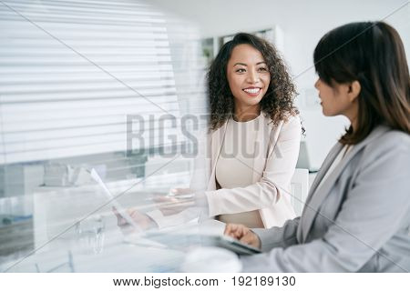 Cheerful middle-aged coworkers sitting at office table and brainstorming on promising project, waist-up portrait
