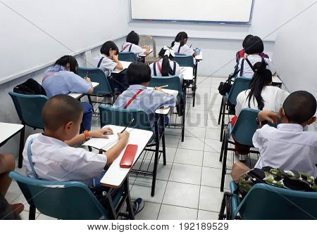 Young Asian students studying after school is over in a small class of a tutorial school.