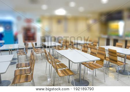Blur of white table and wooden table on food court in shopping mall. food center in department store.