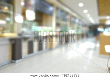 Blur of white table and wooden table on food court in shopping mall. food center in department store