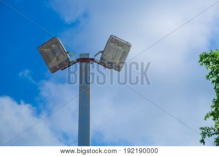 Lamp Post Electricity Industry With Blue Sky Background And Tree. Spotlight Tower.