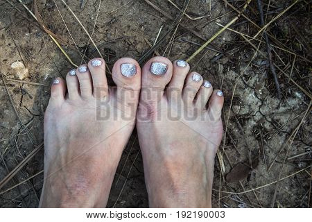 feet of a woman with a pedicure on the ground summer